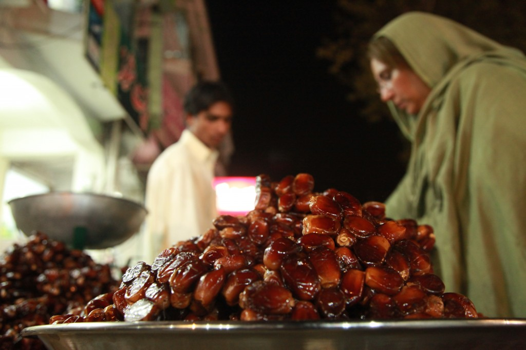 Local woman busy examining the local dates one day before the Moon Sighting day near Karachi Co., Sector G9, Islamabad, Pakistan on July 19, 2012 (KNIZAM OMAR/KNIZAM.COM)